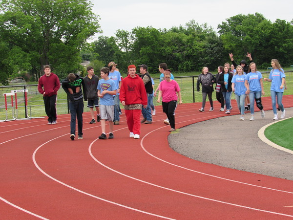 Staff photo by Cathy Spaulding Fort Gibson Middle School students circle the school's running track during a walk-a-thon. The event helped raise money to send soccer balls to African children.