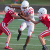 Phoenix special photo by Von Castor<br /> Fort Gibson White's Sammy Sanchez fights off the tackles of Red's Dylan Mills (18) and Connor Brown (22) Tuesday night in the spring Game at Leo Donahue Stadium in Fort Gibson.