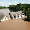 DERRICK JAMES/McAlester News-Capital<br /> Houses along Oklahoma 16 were mostly underwater by Thursday afternoon amid historic flooding in the Verdigris River.