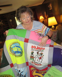 CATHY SPAULDING/Muskogee Phoenix Tamra Scherer admires a quilt she received upon retiring from Muskogee Public Schools. The quilt commemorates her work with Camp Bennett and Special Olympics.