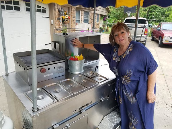 Staff photo by Mark Hughes Janice Woods explains how she keeps all of her wares warm and ready to go in her New York-style hot dog cart. Woods has been bringing the cart to the Muskogee Farmers Market for seven years to sell fried bologna sandwiches, gourmet chicken dogs, Nathan's Famous quarter-pounder hot dogs, and vegan dogs. She said her homemade mint lemonade is made from an old family recipe.