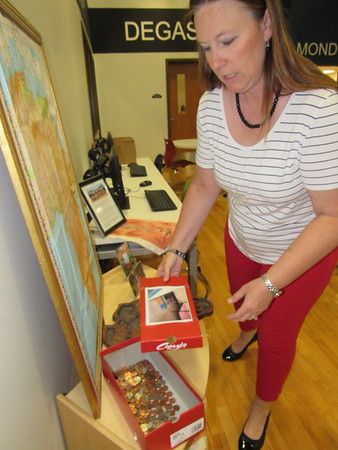 CATHY SPAULDING/Muskogee Phoenix<br /> Sadler Arts Academy media specialist Amanda Cumbey shows coins that continue to be collected for Sadler's Shoes for Kenya campaign. The campaign earned a Promising Practice citation for the school.