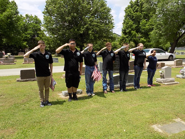 MIKE ELSWICK/Muskogee Phoenix<br /> Some of the 28 Muskogee High School Air Force ROTC students involved in placing American flags on the graves of veterans at Greenhill Cemetery salute after a flag was placed.