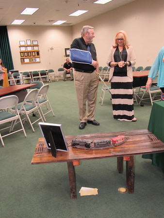 Staff photo by Cathy Spaulding<br /> Jim Wilson, who is retiring as the district's assistant superintendent of support services, and Carla Cooper, an assistant to the superintendent, admire a table that Wilson, a train buff, received as a gift at the reception. It was built with parts from a boxcar.
