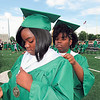 CATHY SPAULDING/Muskogee Phoenix<br /> Chelise Kirby, right, adjusts her twin sister Felise Kirby's graduation stole Friday evening before Muskogee High School Class of 2018 commencement ceremony. The two are going to different colleges after growing up together at the same schools.