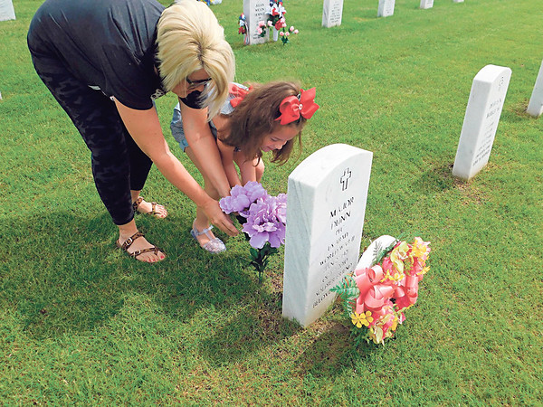 KENTON BROOKS/Muskogee Phoenix<br /> Heather Sheets and her daughter Pyper place flowers at the headstone for her grandparents, Major and Christine Dunn, at the Fort Gibson National Cemetery on Monday. Major Dunn served in the U.S. Army. Pyper Sheets never knew her great-grandparents but said she misses them and accompanied her mother to honor them on Memorial Day.