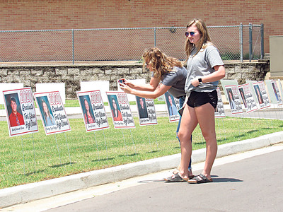 CATHY SPAULDING/Muskogee Phoenix Fort Gibson High School senior Brooklyn Bridges, right, admires yard signs honoring each member of the Class of 2020, while her mother, Mandy Neffendorf, leans to take a photo. The signs were displayed over the weekend at the school district entrance.
