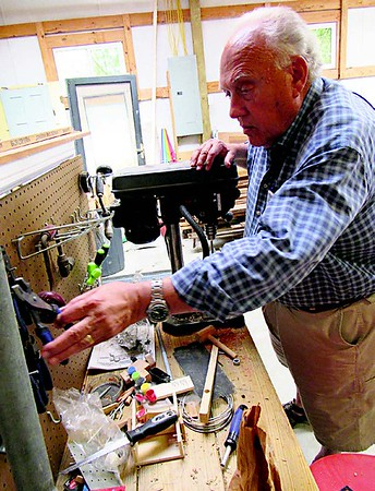 Warren Wagner hangs tools on a pegboard for a work bench he made for his grandson several years ago. He said the grandson likes working there when he's not busy with sports and other activities.