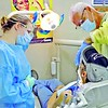 MIKE ELSWICK/Muskogee Phoenix<br /> Rachel Luna, left, and Dr. David Jones work on providing a free teeth cleaning service on Don Dee while Gospel Rescue Mission hosted a mobile dental unit at the site. About 50 people who would likely not have had needed dental services done were able to take advantage of the service, said Rich Schaus, executive director of the mission.