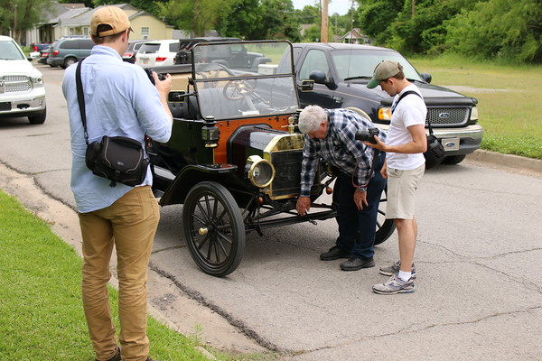 Staff photo by Harrison Grimwood<br /> Ross Staggs, middle, shows Josiah Laubenstein how to crank start Staggs' 1914 Ford Model T Roadster while Darrell Johnston, left, documents the vintage opportunity.