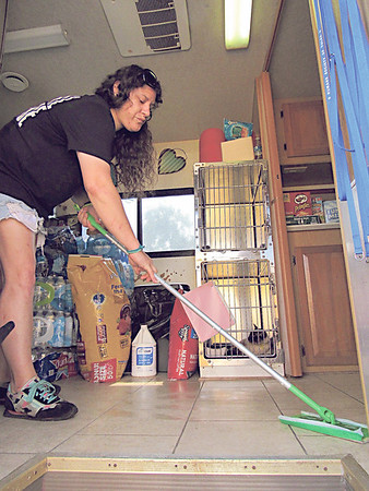 Tulsa Humane Society employee Jennifer King<br /> sweeps a floor inside the Tulsa Humane Society's portable animal shelter while an evacuee's cat, Winter, watches. The shelter was set up to help people at the Red Cross shelter at Bacone College.