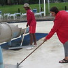 CATHY SPAULDING/Muskogee Phoenix<br /> Lifeguards Adam Stoutermire, left, and Jaci Dotson wipe dirt and storm debris from the children's pool at River Country Family Waterpark. The waterpark will open for the season on Monday along with Spaulding Pool and splash pads at Honor Heights, Civitan, Elliott, Robison, Beckman and Rotary parks.
