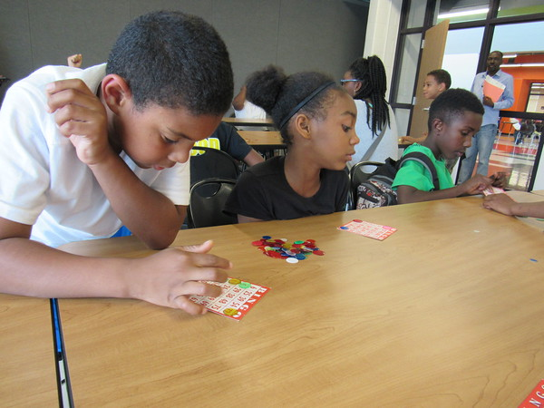 Staff photo by Cathy Spaulding<br /> Mychael Simpson, 7, left, studies how he almost scored a Bingo, while 10-year-old Chiyeanne Reed, second left, and other players shout their successes during a game at the new Dr. Martin Luther King Jr. Community Center. The center is three times larger than the former building with more space for summer activities that kick off Tuesday.