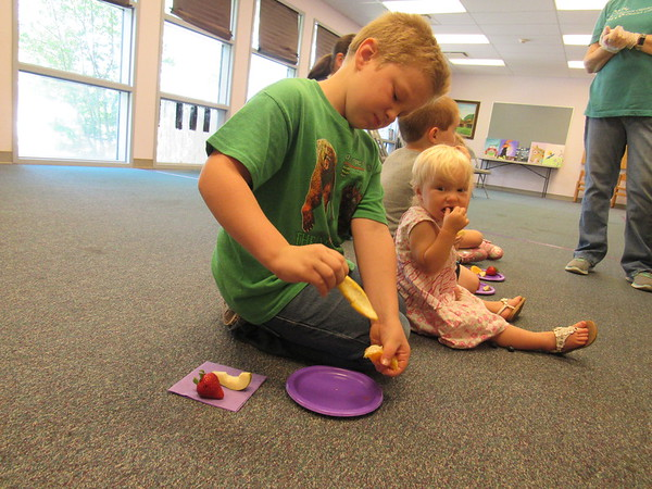 """CATHY SPAULDING/Muskogee Phoenix<br /> Jackson Ottenbacher, 7, peels an orange slice while his 18-month-old sister Autumn nibbles on berries. They came to Q.B. Boydstun Library on Thursday to sample foods eaten by """"The Very Hungry Caterpillar."""""""