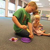 "CATHY SPAULDING/Muskogee Phoenix<br /> Jackson Ottenbacher, 7, peels an orange slice while his 18-month-old sister Autumn nibbles on berries. They came to Q.B. Boydstun Library on Thursday to sample foods eaten by ""The Very Hungry Caterpillar."""