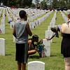 MIKE ELSWICK/Muskogee Phoenix<br /> As others watch, Angelia Lax, kneeling left, and Princella Nicholson, right, both of Muskogee, touch the headstone and say a prayer at the grave of James Nicholson on Monday after Memorial Day ceremonies at Fort Gibson National Cemetery. He was a veteran of the U.S Air Force who died Dec. 2, 1999.