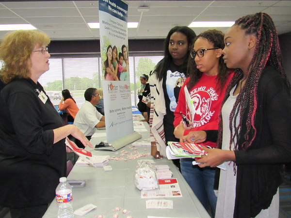 Staff photo by Cathy Spaulding<br /> Lori Tibbs, left, an outreach coordinator for Porter Health Center and Muskogee Health Center, visits with Muskogee High School students, from second left, Annise McNac, Iyesha Maxwell and Kariauna Birmingham at the Indian Capital Technology Center's job fair. About 70 vendors were represented.