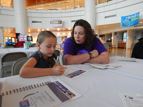 Staff photo by Wendy Burton<br /> Cancer survivor Tiffany McCoin, right, helps her daughter Kindrie, 7, fill out a survivor's story form about her mother during the Relay for Life Honoring Dinner Tuesday evening. The Relay for Life Fundraiser for the American Cancer Society will be held beginning at 6 p.m. Friday at the football stadium behind Alice Robertson Junior High. All are welcome to attend.