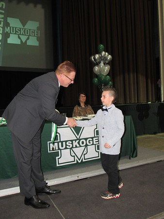 CATHY SPAULDING/Muskogee Phoenix<br /> Muskogee Public Schools Superintendent Dr. Jarod Mendenhall congratulates Creek Elementary student Jacob Galloway during the 2019 Academic Honors Banquet, held Thursday at Muskogee Civic Center.