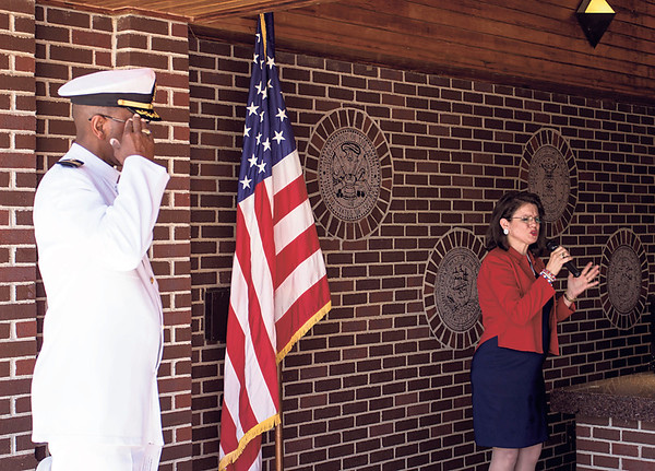 Special photo by Travis Sloat<br /> Chaplain Forrest Kirk of the Jack C. Montgomery VA Medical Center stands at attention as Colleen Thompson sings the national anthem at Monday's ceremony.