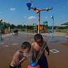 KENTON BROOKS/Muskogee Phoenix<br /> As the temperature climbed into the 90s, Isaac Garcia, left, and his brother Joel Sandoval take a break from the heat for a water break during their play time at Robison Park.