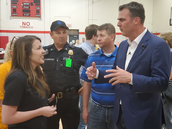 CHESLEY OXENDINE/Muskogee Phoenix<br /> (From left) Organizer Haley Norman, joined by Fort Gibson Police Chief Donnie Yarbrough and Oklahoma Senator Chris Sneed, speaks with Governor Kevin Stitt during a visit to Fort Gibson's flood relief resource center.