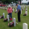 Staff photo by Mark Hughes<br /> Ruby and Eugene Dye place flowers at the headstones of two of his five brothers Monday at the Fort Gibson National Cemetery. All five, plus Dye, served in the military.
