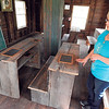 Staff photo by Mark Hughes<br /> Sue Tolbert, director of Three Rivers Museum, talks about the benches that black grade school students may have used from the 1920s to 1950 at Oak Grove School. The school was originally called Oak Grove Separated School and would have provided education to about 20 students.