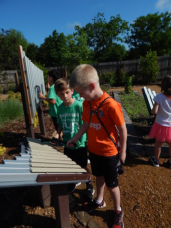 KENTON BROOKS/Muskogee Phoenix<br /> Easton Neves, right, strikes one of the musical instruments and Kooper Willey listens at the Beatrice Sheddan Children's Garden by the Papilion in Honor Heights Park.