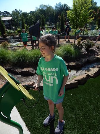KENTON BROOKS/Muskogee Phoenix<br /> Libby Deshazo, a second-grader at Fort Gibson Early Learning Center, plays one of the musical instruments at the Beatrice Sheddan Children's Garden by the Papilion in Honor Heights Park.