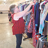 CHESLEY OXENDINE/Muskogee Phoenix<br /> Beth Thompson inspects a rack of donated clothing in the dining hall at the Masonic Lodge Thursday morning. Thompson, alongside the Order of the Eastern Star, has been collecting clothing for flood victims since Sunday.