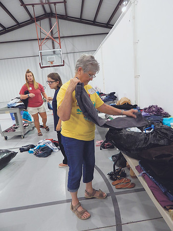 KENTON BROOKS/Muskogee Phoenix<br /> Volunteer Betty Buford folds clothes in the First Baptist Church of Warner Family Life Center Thursday. The church opened its doors to help the people in Webbers Falls affected by the flooding. Clothing, non-perishable food and other necessities were available for people to pick up. The church had helped 150 families through Thursday, Lead Pastor Sam Dunn said.
