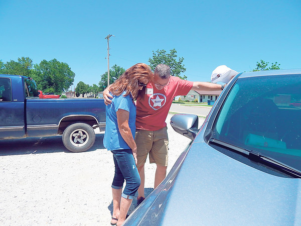 KENTON BROOKS/Muskogee Phoenix<br /> Pastor Sam Dunn, right, prays with Linda Reece Thursday outside the First Baptist Church of Warner after Reece picked up food and supplies for her daughter.