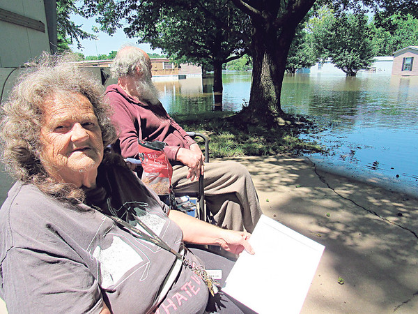 CATHY SPAULDING/Muskogee Phoenix<br /> Riverside Mobile Home Park residents Beverly Liles and Ronnie Graves sit by flooded lots next to theirs.