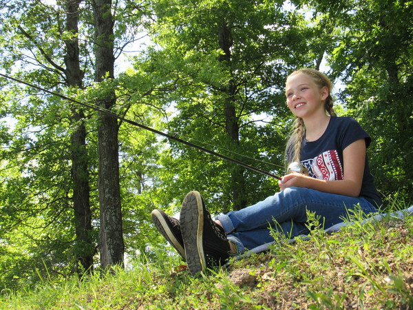 Staff photo by Cathy Spaulding<br /> Warner fifth-grader Elyssa Bales finds a shady spot to fish during Tuesday's Gentry Creek Fishing Fling. Students learned water safety as well as fishing tips.