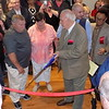 MIKE ELSWICK/Muskogee Phoenix<br /> The Miller Family Center for Life Change hosted a ribbon cutting ceremony before a full house inside the lobby of the newly renovated facility which will be the new home for the Gospel Rescue Mission. Holding the ceremonial scissors is David Miller while Nancy Cox Horne, center, who is a descendant of the founding Cox family, and her husband Steve Horne from Land O'Lakes, Florida, look on.