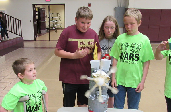 CATHY SPAULDING/Muskogee Phoenix<br /> Warner fifth-graders, from left, Phillip Sorg, Jon Brown, Amnesty Marlmee and Elijah Gifford coax some action out of their wind-powered lifting machine. The machine lifted a 10-gram weight during the STEM Wars science competition Friday.