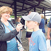 KENTON BROOKS/Muskogee Phoenix<br /> Leslie Mansfield, left, of Fort Gibson, offers her grandson Weston a sample of the yogurt parfait they found at the Farmers Market on Saturday. The market, open on Wednesdays and Saturdays, is in its 24th year.
