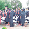 KENTON BROOKS/Muskogee Phoenix<br /> Bacone College graduates stand for the national anthem at Saturday's commencement ceremony in front of the Bacone Chapel on Saturday. A total of 63 graduates received degrees from as close as Oktaha and as far away as the Cayman Islands.