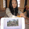 CATHY SPAULDING/Muskogee Phoenix<br /> Yuree Lembke shows a photo of a Burmese refugee camp, similar to ones she grew up in. She and her husband are raising money to help refugees.