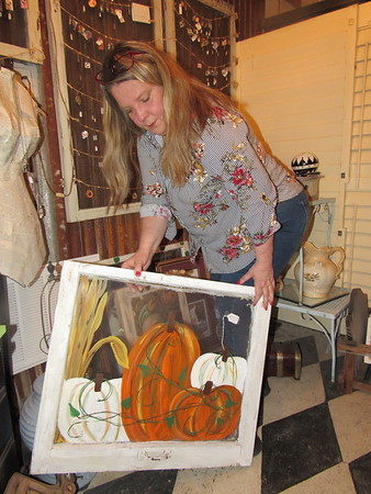 """Miriam Sommers shows a painted window pane she has at her Hattie's House booth """"My Sister's Charms."""""""