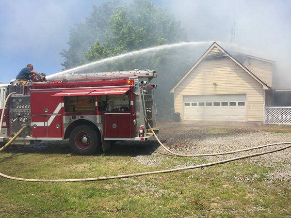 Staff photo by D.E. Smoot<br /> Keefeton firefighter Brandon Drake blankets a house with water Thursday, knocking down the flames that consumed much of a two-story house in a rural neighborhood south of Muskogee.