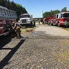 Staff photo by D.E. Smoot<br /> Tanker trucks queue along the driveway Thursday, priming pumper trucks used to extinguish the blaze. The home's owner complained that the nearest hydrants were too far from the scene.