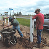 KENTON BROOKS/Muskogee Phoenix<br /> Jerry Burke of Checotah's Mann's Pioneer Fence prepares to shovel wet concrete into a hole to solidify a post for the white ranch rail fence being erected in Checotah as Tyler Mann holds the post and Rodney Millican watches.