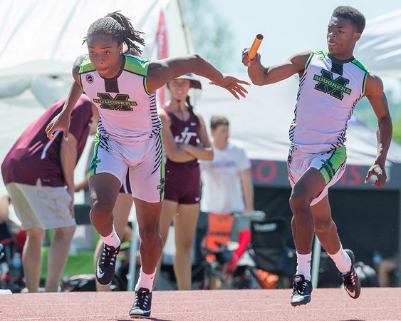 Phoenix special photo by Von Castor<br /> Muskogee's Donald Mayes hands the baton off to John Smith in the boys 400-meter relay at the 6A regional at Claremore Saturday afternoon.