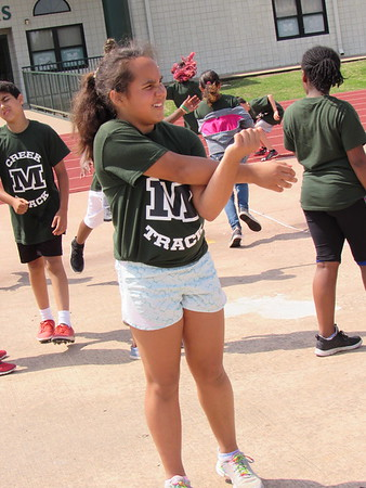 CATHY SPAULDING/Muskogee Phoenix<br /> Jaylee Sallis of Creek Elementary stretches her arms before competing.Students from each elementary school in Muskogee Public Schools tried their skills at various events Monday during the annual Elementary Track Meet.