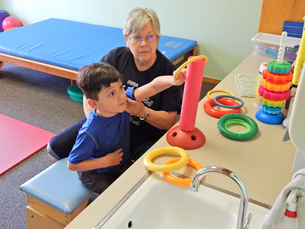 Staff photo by Mark Hughes<br /> Beau McKenna, 8, reaches to place a rubber ring over a pole as part of his exercise program to combat cerebral palsy as Pat Pack steadies him at the Kelly B. Todd Cerebral Palsy and Neuro-muscular Center, where Pack is the director of clinical physical therapy. The center provides free services to children with cerebral palsy and other neuromuscular issues.