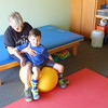 Staff photo by Mark Hughes<br /> Pat Pack assists Beau McKenna in his range of motion that will help him use his back muscles to sit up without needing to use his arms to prop himself.
