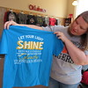 Staff photo by Cathy Spaulding<br /> LouAnn Fore shows a T-shirt sold as a fundraiser to help retired teacher Tammy Delmedico battle breast cancer. Fore said the verse, Matthew 5:16, is Delmedico's favorite passage.