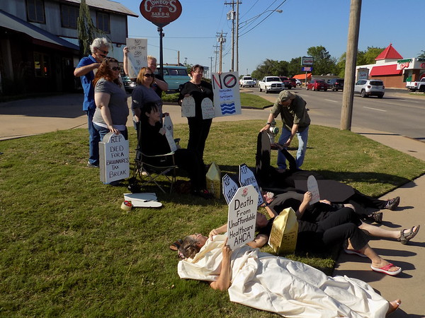Special photo by Mike Elswick<br /> About a dozen people protest U.S. Rep. Markwayne Mullin's appearance Monday at the Muskogee County Republican Party meeting at Cowboy's BBQ on North York Street and the Westville Republican's support of the American Health Care Act.